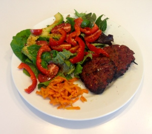 Healthy lamb burger patty with salad and fermented carrot kraut